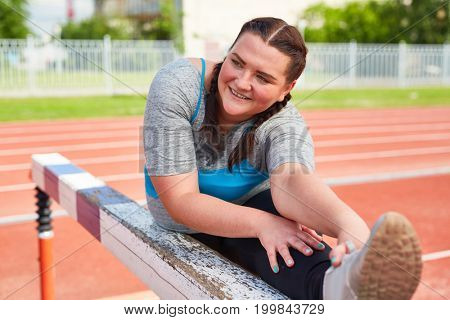 Young oversized woman making effort while doing stretch exercise on stadium