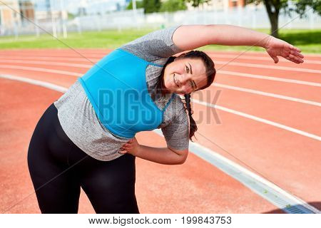 Active overweight woman exercising on stadium at leisure