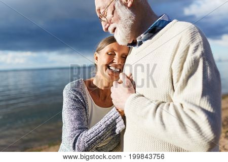Happy aged man and woman having romantic weekend by the seaside