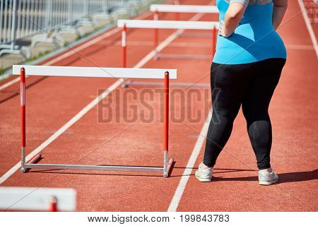 Determined plus-size female in activewear standing by hurdle on racetrack