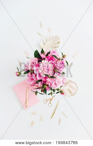 Flat lay home office desk. Female workspace with pink peonies bouquet golden accessories pink diary on white background. Top view feminine background.
