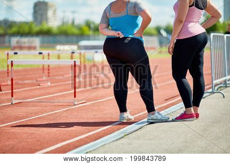Two plump friends in sportswear standing on racetrack of stadium
