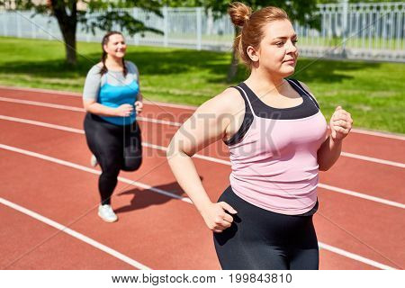 Active and determined over-sized women jogging on stadium in the morning