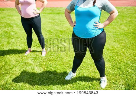 Two over-sized females standing akimbo on the grass during workout
