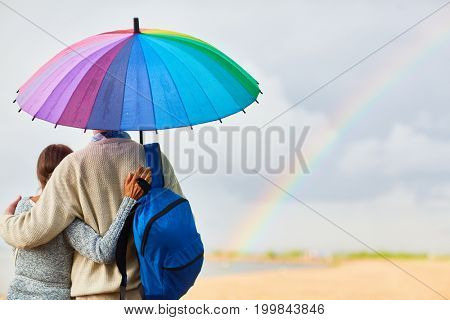Back view of tourists with backpack standing under colorful umbrella in rural environment