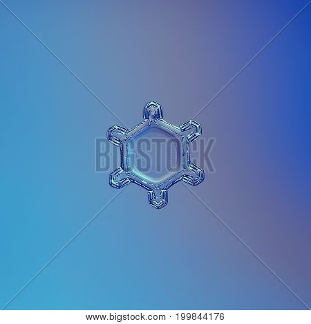 Real snowflake macro photo: small and simple snow crystal with six tiny arms and large, flat central hexagon with complex inner pattern of tiny dots. Snowflake glittering on blue gradient background.