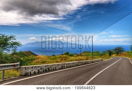 Newly asphalt road on the island of Fogo descends towards the capital city with sister island of Brava in view at sea.