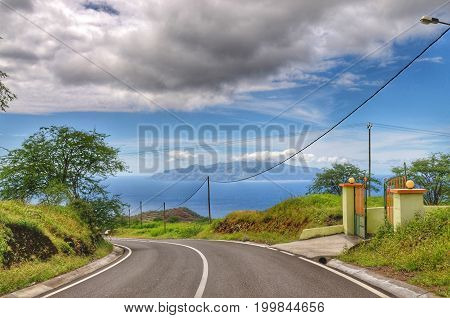 Asphalt road makes its way towards the city of Sao Filipe in Fogo Cab Verde as it curves by a entry gate