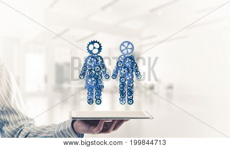 Close of businessman holdingn tablet pc with figures of man and woman made of gears. Mixed media