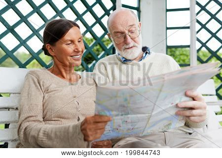 Senior tourists choosing route of their further travel while sitting on bench