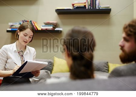 Young counselor writing down story of married couple surviving hard times