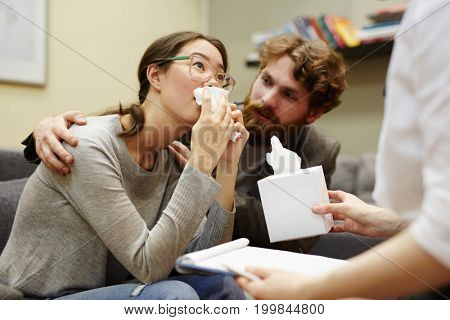Crying woman with handkerchief looking at counselor while young man supporting her