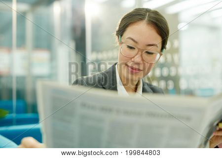 Young employee in eyeglasses reading latest news in the morning