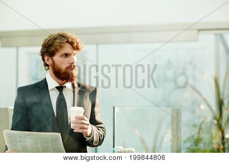 Businessman with drink and newspaper contemplating in office