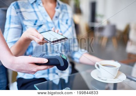Close-up shot of unrecognizable woman using mobile phone in order to pay for her coffee at lovely cafe, close-up shot