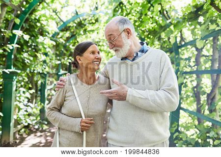 Restful seniors enjoying walk in the countryside or spending their weekend in natural environment