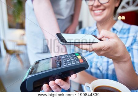 Close-up shot of smiling female visitor of restaurant paying for her coffee with smartphone, blurred background