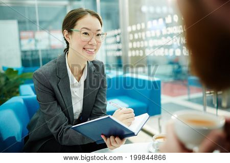 Smiling young woman in formalwear and eyeglasses making notes during conversation with business partner or client