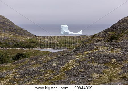 iceberg by the hilly rocky coastline of Fogo Island, Newfoundland