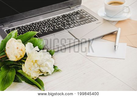 Side view of a deck with computer bouquet of peonies flowers cup of coffee empty card and kraft envelope. White rustic wooden background. Romantic and feminine outlook.