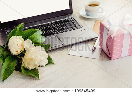 Side view of a deck with computer bouquet of peonies flowers cup of coffee empty card and pink dotted gift box. White rustic wooden background. Romantic and feminine outlook.