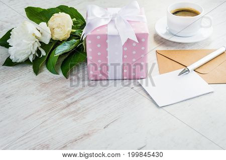 Pink dotted gift box empty greeting card kraft envelope peonies bouquet and coffee cup over white wooden rustic table. Romantic holiday and event concept
