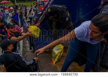 Quito, Ecuador - April, 17, 2016: Crowd of people of Quito providing disaster relief food, clothes, medicine and water for earthquake survivors in the coast.