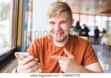 technology, communication and people concept - Young man holding smartphone.