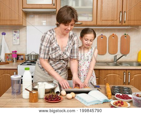 Woman and child girl preparing flour for baking and cookies on a wooden background. Raw food and kitchen utensils. Break an egg, cooking dough.