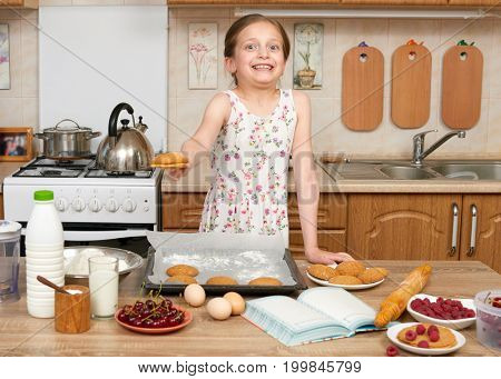 Child girl baking cookies in home kitchen. Raw food and fruits. Healthy food concept.