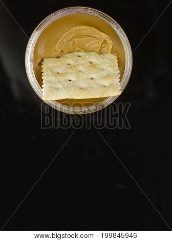 A Saltine Cracker Half Way in Jar of Peanut Butter