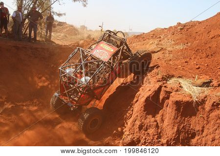 Red Car Ramping Out Of Steep Dugout, Front Wheels Suspended