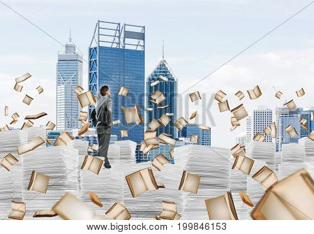 Confident businessman in suit standing on pile of documents among flying books with cityscape on background. Mixed media.