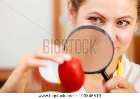 Mature woman female inspecting testing tomato food with magnifying glass.