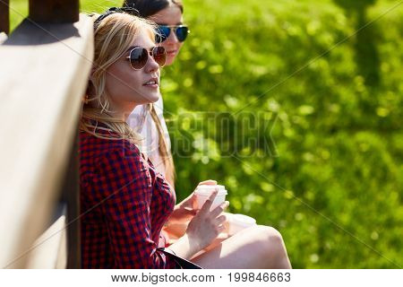 Friendly girls with drinks relaxing outdoors on hot sunny day