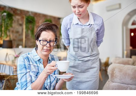 Middle-aged woman wearing checked shirt making wry face due to unsavory coffee, young red-haired waitress standing next to her with worried expression