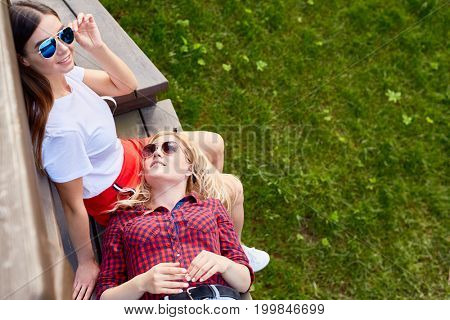 Pretty serene girls having rest on wooden bench in natural environment