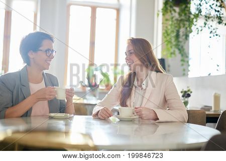 Cheerful white collar workers chatting animatedly with each other while having coffee break, interior of lovely cafe on background