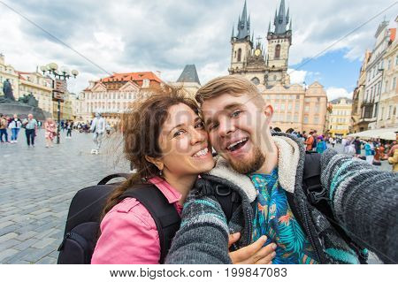 Happy romantic couple of tourists makes selfie self-portrait in Prague while traveling across Europe