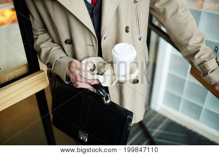 Elegant man in trenchcoat opening door of cafe and leaving it after buying takeout drink