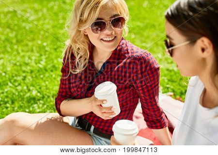Girlfriends in sunglasses having drinks on hot summer day in the park