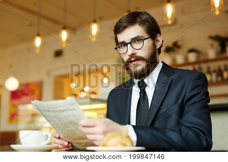 Unemployed man with newspaper reading adverts while hunting for job