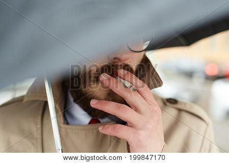 Posh young man under umbrella smoking cigarette