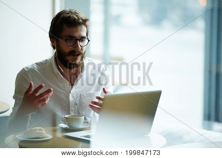 Young specialist with earphones talking to employer through video-chat during online interview