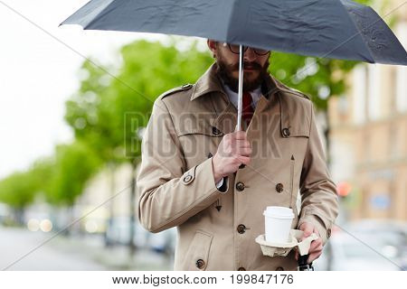 Stylish businessman carrying glass of drink and umbrella whle walking down the street