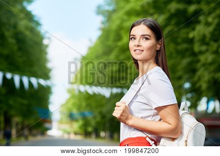 Young woman with rucksack thinking where to go in the park