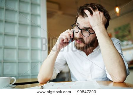 Anxious young man speaking to employer on smartphone while looking for job