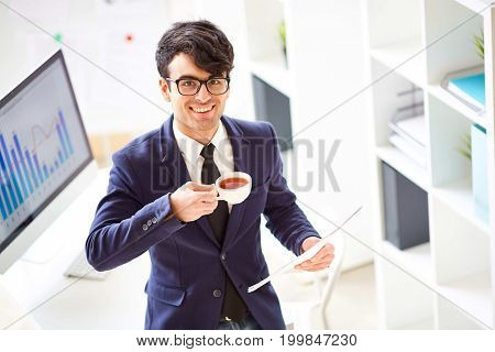 Smiling manager with cup of tea and papers standing by workplace in office