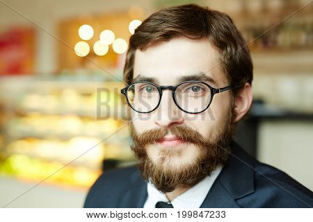 Confident young man in eyeglasses sitting in cafe at break