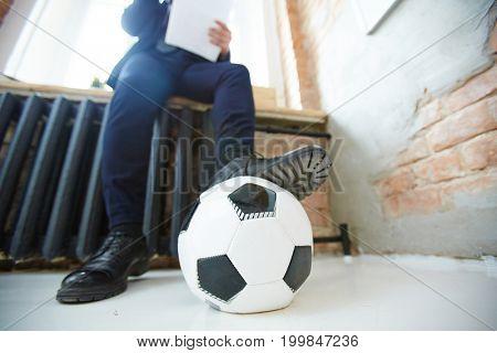 Soccer ball on the floor under leg of working businessman